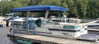An older Harris pontoon boat with a 50 hp engine.